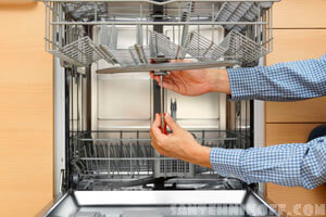 Мастер устанавливает, ремонтирует посудомоечную машину