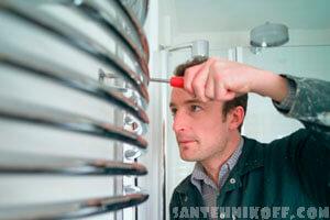 Сантехник меняет полотенцесушитель в ванной